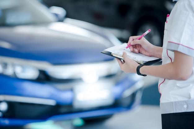 車のセールスマンは、営業担当者のショールームで車の在庫を記録しています。 Premium写真
