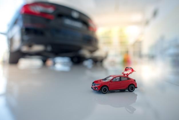 Маленький красный седан и финансовый отчет с монетами. авто финансы и кредиты, сэкономьте деньги на идеи дизайна автомобилей или материалы Premium Фотографии