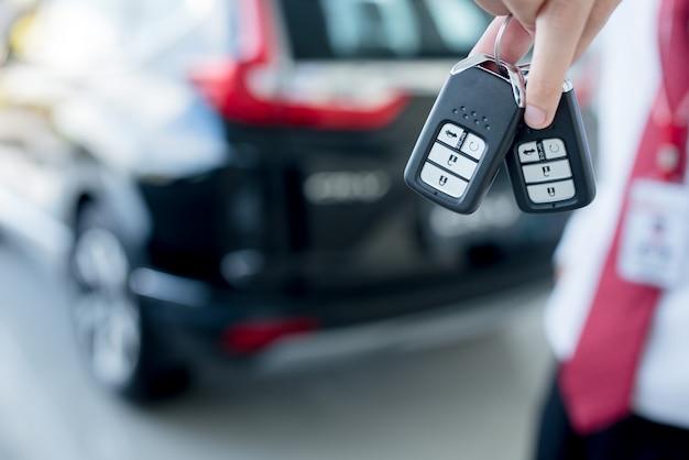 車のキー-車のショールーム、新しいキーで新しい車のキーを保持している若い男のクローズアップ Premium写真