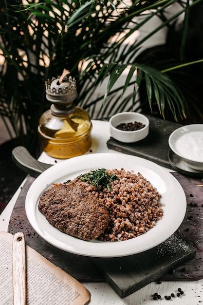 テーブルの上の肉のカツレツとハーブとそばの側面図 無料写真