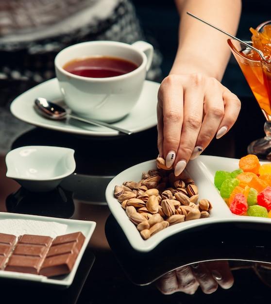 Белая чашка чая подается с шоколадом, фисташками Бесплатные Фотографии