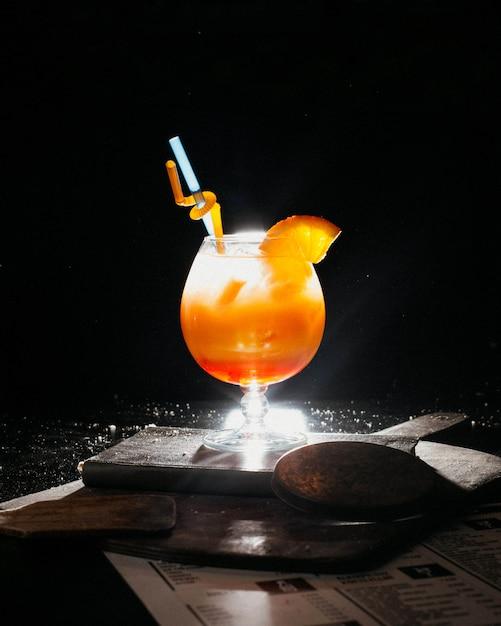 Апельсиновый коктейль со свежим апельсиновым соком, льдом и соломкой на книге Бесплатные Фотографии