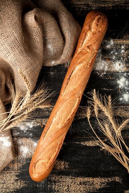 テーブルの上の小麦粉と小麦のバゲットのパン 無料写真