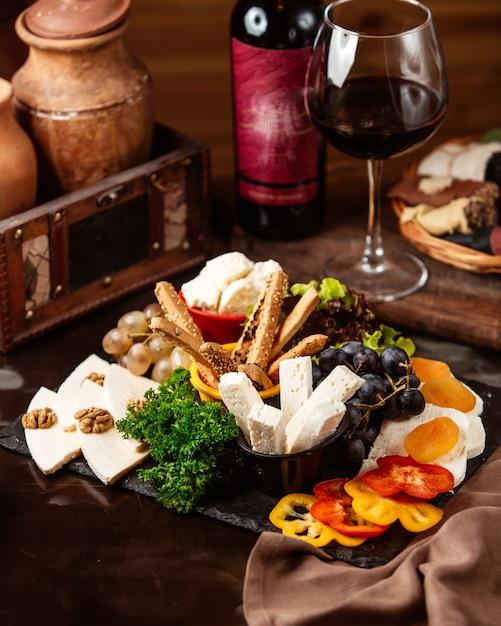 ブドウと赤ワインのガラスのサイドビューチーズプレート 無料写真