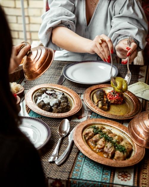 サイドビューの女の子がドルマとキャベツロールをヨーグルトで食べる 無料写真