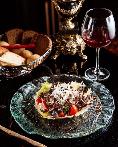テーブルの上の赤ワインのプレートに野菜とパルメザンチーズのビーフサラダの側面図 無料写真