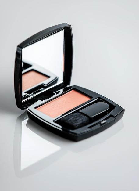 Коробка для румян спереди с кисточкой и небольшим зеркалом на белой поверхности Бесплатные Фотографии