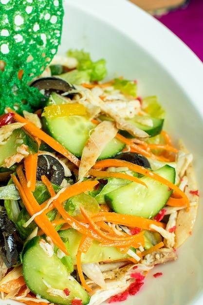 Крупным планом вид куриный салат с нарезанные свежие овощи и черные оливки в миску Бесплатные Фотографии