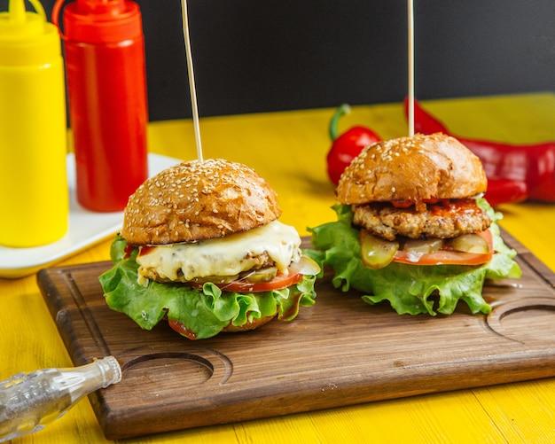 Вид сбоку бургеры с плавленым сыром и помидорами куриные котлеты на деревянной доске Бесплатные Фотографии