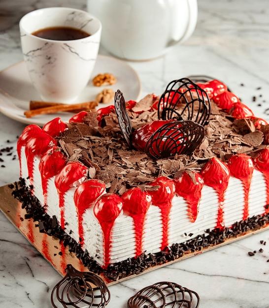 お茶を添えてテーブルの上のチョコレートフレークをのせたフルーツケーキの側面図 無料写真