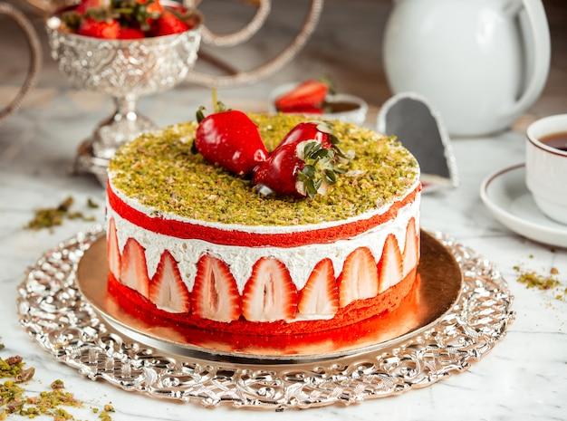 テーブルの上のピスタチオのパン粉とイチゴのケーキの側面図 無料写真