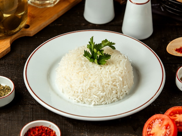 Вид сбоку тарелки с вареным рисом с петрушкой на столе Бесплатные Фотографии