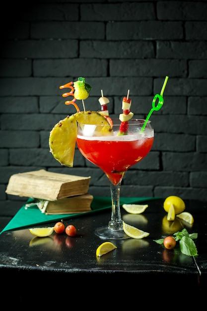 テーブルの上のガラスのパイナップルに赤いエキゾチックなアルコールカクテルの側面図 無料写真