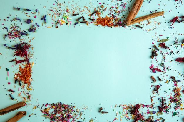 シナモンスティックと様々なスパイスと青のコピースペースと乾燥した花びらの側面図 無料写真