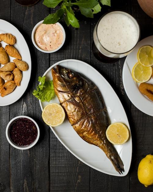 スモーク魚のレモン添え 無料写真