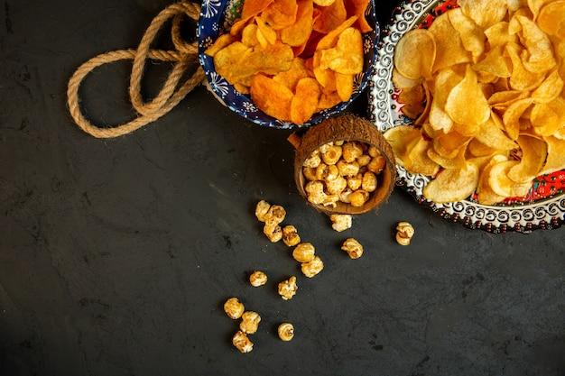 Вид сверху картофельные чипсы и попкорн в тарелку с восточным узором на черном Бесплатные Фотографии