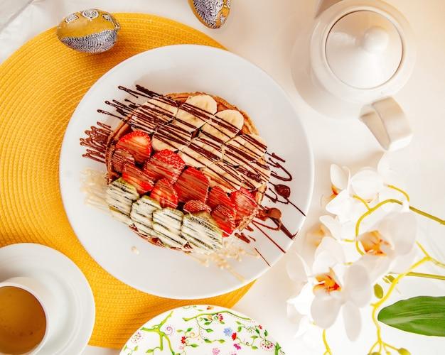 Вид сверху на тонкий блин с клубникой, бананами и киви в шоколадном соусе в белой тарелке Бесплатные Фотографии
