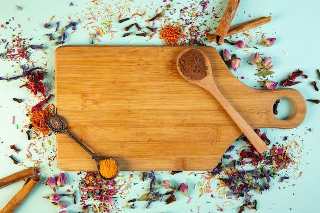 青のシナモンパウダースプーンで木製のまな板の上から見る 無料写真
