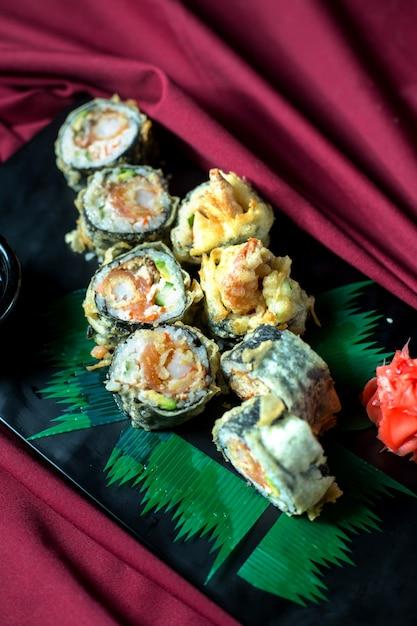 Вид сверху японской традиционной еды темпура суши маки подается с имбирем и соевым соусом на черной доске Бесплатные Фотографии