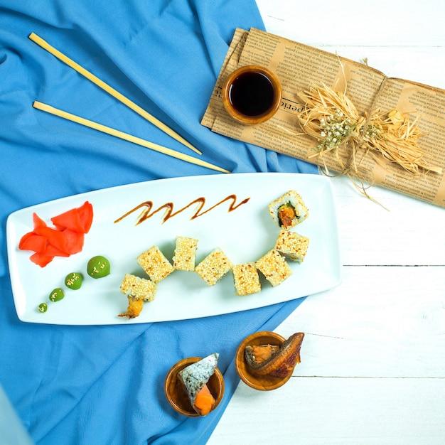 Вид сверху традиционной японской кухни суши ролл с рисовыми креветками, авокадо и сливочным сыром, подается с имбирем в соевом соусе и васаби на синем и белом Бесплатные Фотографии