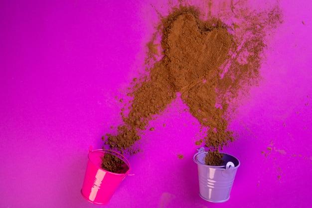 Вид сверху порошка корицы, разбросанного из маленьких ведер в форме сердца на фиолетовый Бесплатные Фотографии