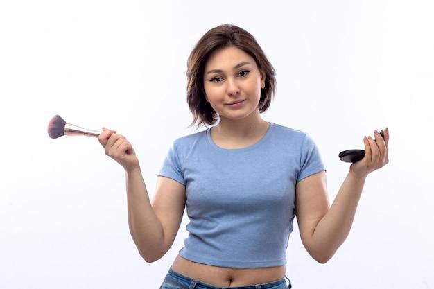 Молодая женщина в синей рубашке, делать макияж Бесплатные Фотографии