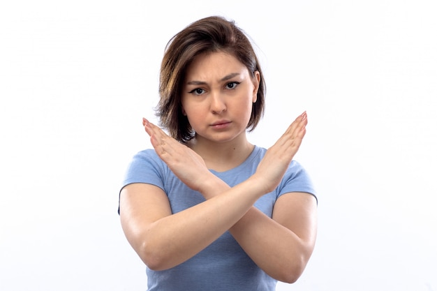 Молодая женщина в синей рубашке, показывая знак остановки Бесплатные Фотографии