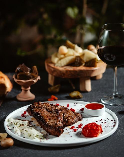 白い皿にケチャップと新鮮な玉ねぎと牛肉のグリルステーキの側面図 無料写真