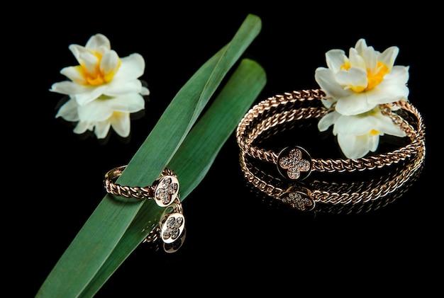 ゴールデンブレスレットとダイヤモンドリングのジュエリーセットの側面図 無料写真