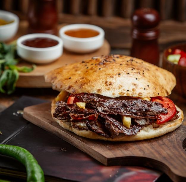 ジャガイモを詰めたパンとビーフドナー、木板で提供するフライドポテト 無料写真
