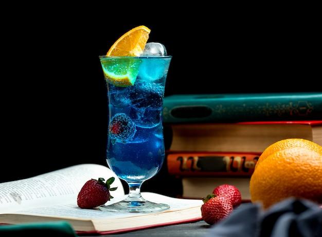 ブラックベリー、オレンジスライス、イチゴ、氷と青いカクテル 無料写真