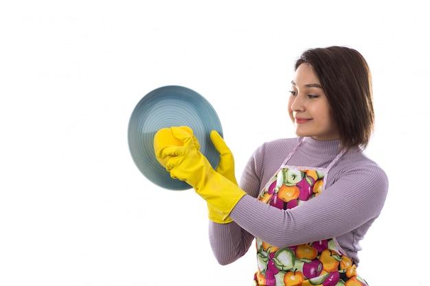 お皿を洗うカラフルなエプロンを持つ女性 無料写真