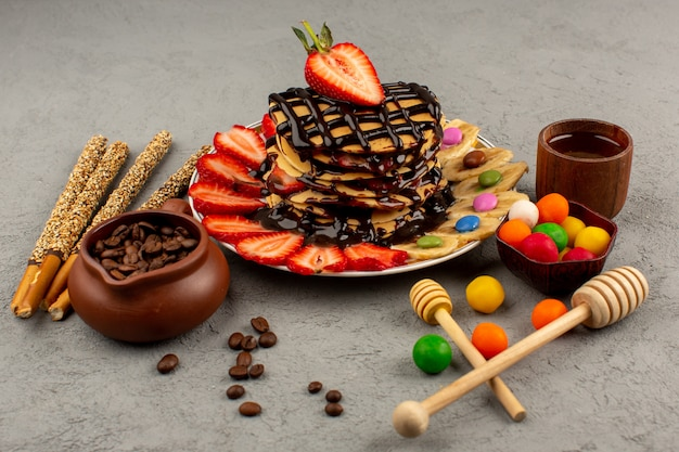 正面のパンケーキおいしいおいしいチョコとスライスした赤いイチゴと灰色の背景に白いプレート内のバナナ 無料写真