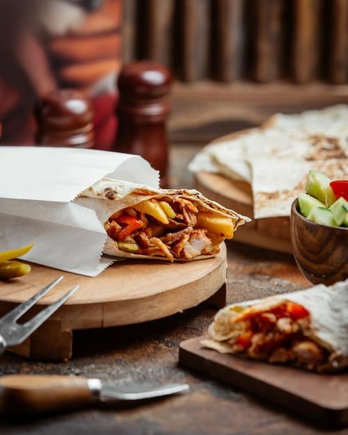 Обертка из куриной лепешки с картофелем фри, помидорами, колючками в бумажном пакетике на вынос Бесплатные Фотографии