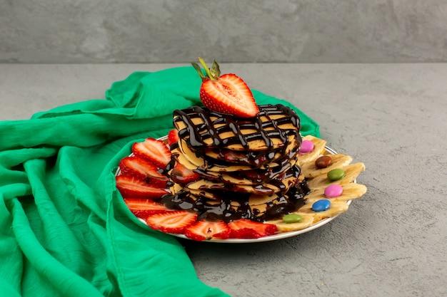 チョコレートスライスした赤いイチゴと灰色の床に白いプレート内のバナナとおいしいパンケーキを正面から見る 無料写真