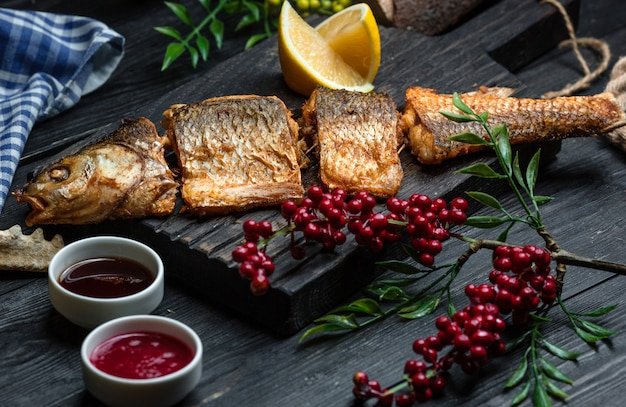 木の板にクランベリーと魚のフライ 無料写真