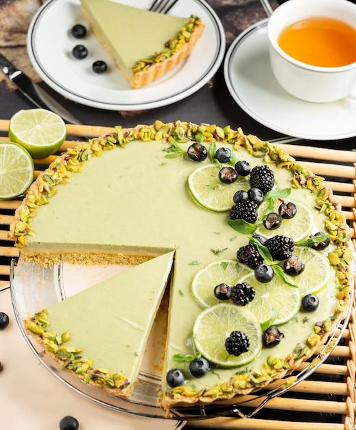 ライムスライス、ブラックベリー、ブラックカラント、ピスタチオを添えたライムチーズケーキ 無料写真