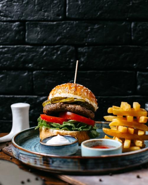 Вид сбоку бургер с картофелем фри, кетчупом и майонезом на подносе Бесплатные Фотографии
