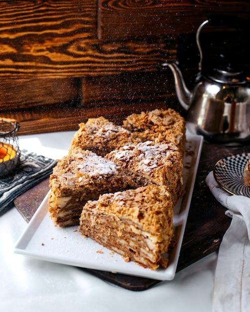 正面のおいしいケーキは茶色の床に白いプレート内のおいしいスライス 無料写真