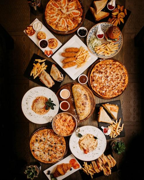 茶色の表面に美味しいおいしいさまざまなペストリーや料理のトップビューの食事 無料写真