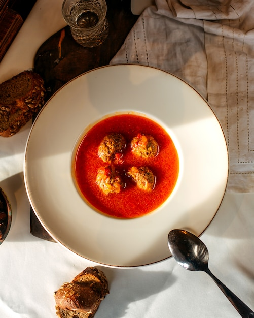 Вид сверху суп с мясом помидор вместе с ломтиками хлеба на белом полу Бесплатные Фотографии