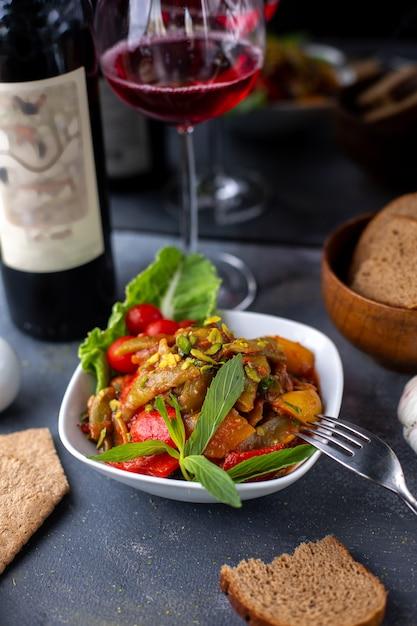 フライドポテトと新鮮な野菜サラダと灰色の机の上の赤ワイン 無料写真