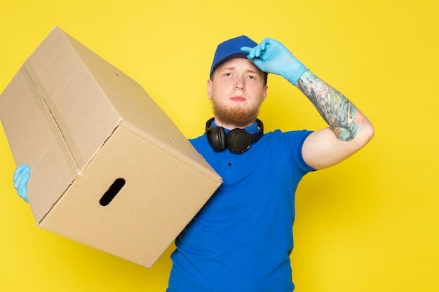 Молодой доставщик в голубой поло синяя кепка белый джинсовый рюкзак держит коробку на желтом Бесплатные Фотографии