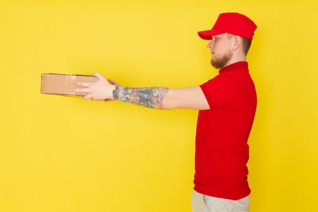 黄色のボックスを保持している赤いポロ赤い帽子白いジーンズの若い配達人 無料写真