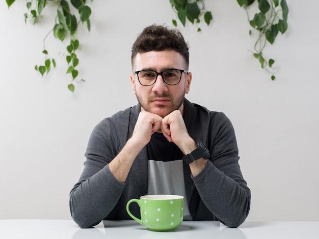 Молодой человек, сидящий в очках, смотрит серый пиджак вместе с растением на белом Бесплатные Фотографии