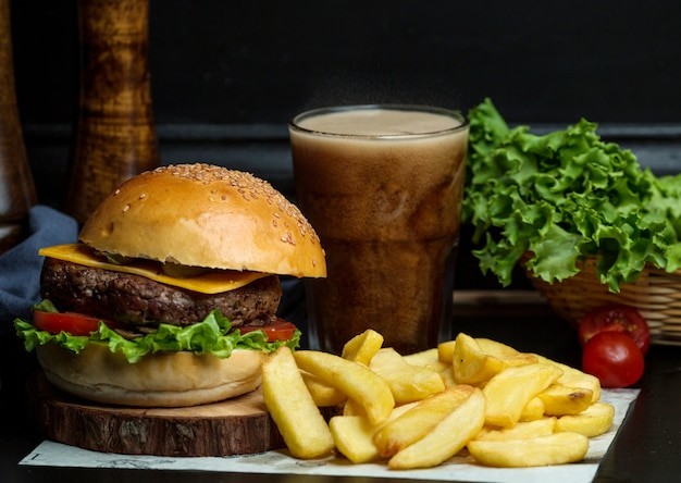 Бургер из говядины с сыром, листьями салата, помидорами, подается с картофелем фри и колой Бесплатные Фотографии