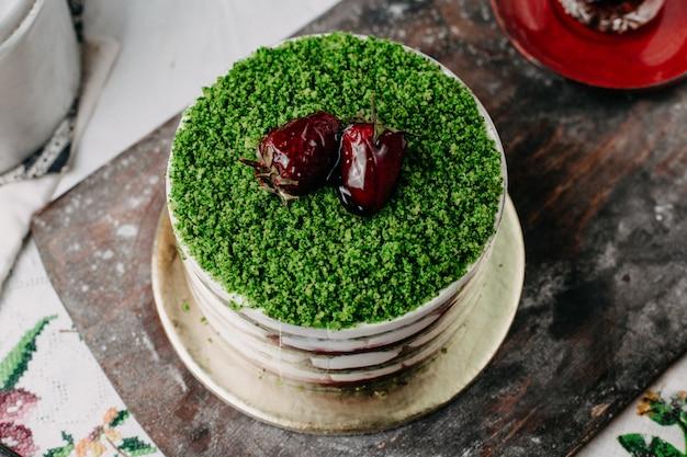 灰色の机の上のおいしいおいしい丸いスライスフルーツとグリーンケーキ粉末フルーツケーキ 無料写真