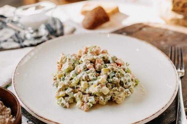 Майонез овощной салат соленый вкусный внутри белая тарелка вместе с вилкой для буханок хлеба в дневное время Бесплатные Фотографии
