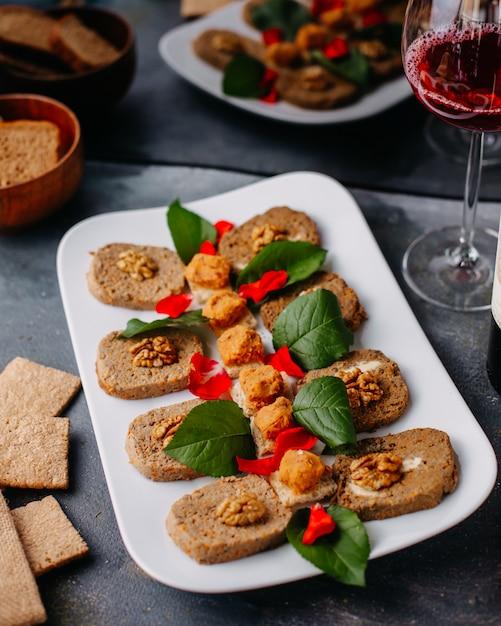Овощной паштет, сформированный вместе с зелеными листьями внутри белой тарелки вместе с чипсами из красного вина на сером Бесплатные Фотографии