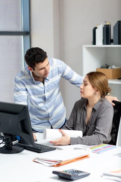 Вид спереди молодая красивая дама в серой рубашке разговаривает и обсуждает что-то с молодым человеком в офисе во время дневного строительства Бесплатные Фотографии